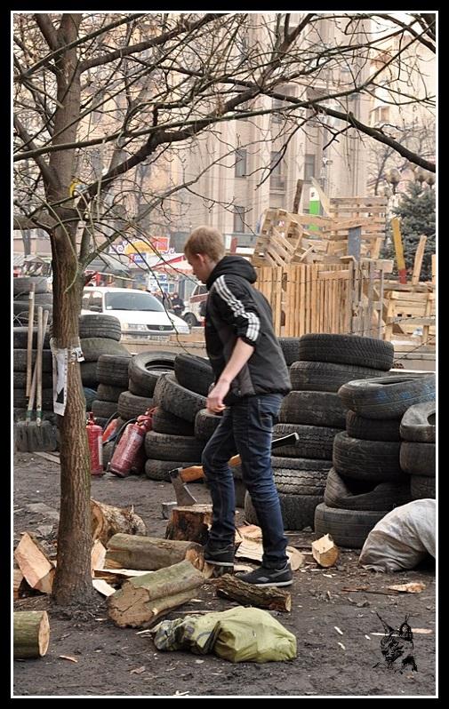 Kiev - Révolution de 2014 Euromaidan - Place de l'indépendance - jeune coupant du bois
